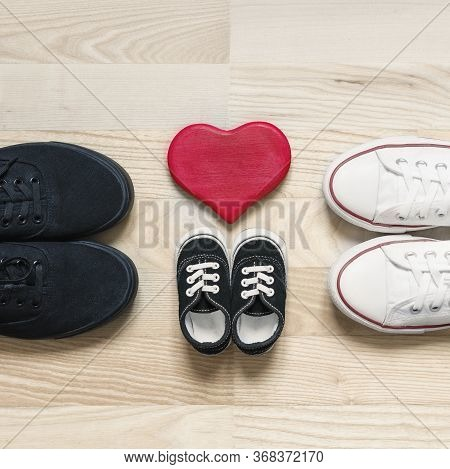Happy Family Concept. Father, Mother And Little Kid Shoes On Wooden Floor With Red Heart. Symbol Of