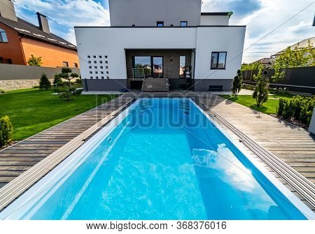 Natural Garden With Water Pool In Luxurious House. Garden On The Background. Pool With Clean Water.