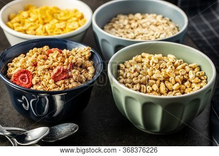 Various breakfast cereals in bowls. Puffed wheat and oatmeals.