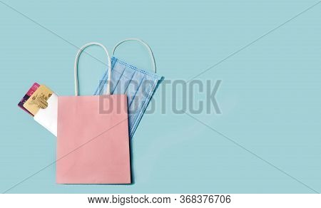 Online Shopping Concept. A Package For Purchases With Bank Cards And A Medical Mask For Protection O