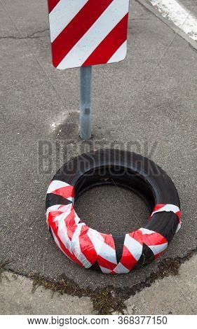 Old Tire Cover (wheel) Wrapped In Red And White Safety Strip. Self-made Attention And Danger Signal.