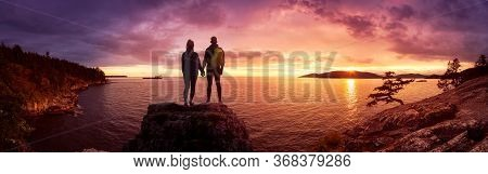 Fantasy Adventure Composite Of A Man And Woman Couple On A Rocky Coast During A Colorful Dramatic Su