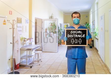 Male Doctor In Scrubs With Protective Face Mask, Holding Blackboard With Chalk Handwriting Social Di