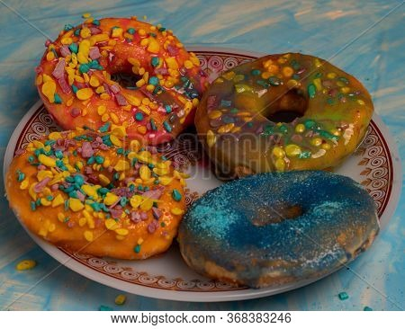 Orange Donuts With Many Colored Shavings On A Plate With Colored Caramel