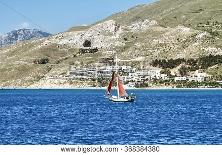 Yacht With Red Sails Off The Coast Of The Island Of Kos. Greece