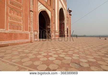 Woman Looking Up At The Taj Mahal Mosque Red Sandstone Facade, Near The Mughal Tomb Landmark, Agra,