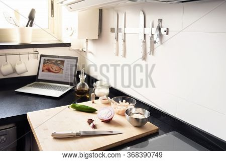 Laptop Computer With Recipe With Ingredients And Cooking Utensils On The Worktop At The Kitchen, Con
