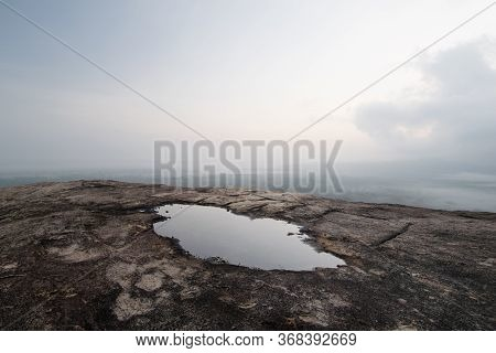 Barren Rock And Puddle. Panorama Shot Of The Sunrise Sky And Its Reflection In A Puddle Of Water, Fr