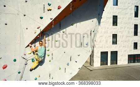 Young Woman Rock Climber Climbing On Vertical Artificial Rock Wall In Outside Climbing Gym