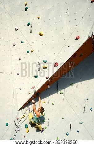 Sporty Woman Practicing Rock Climbing On Artificial Rock Wall In Climbing Gym. Making Hard Move And