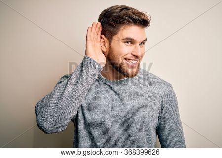 Young handsome blond man with beard and blue eyes wearing casual sweater smiling with hand over ear listening an hearing to rumor or gossip. Deafness concept.