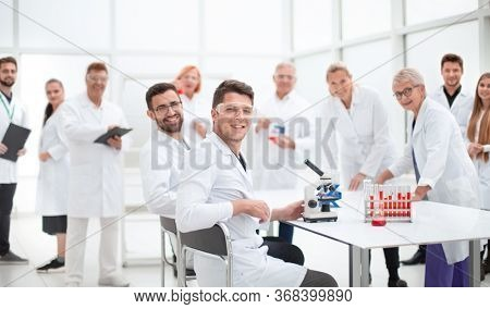 young scientist and his colleagues work in the laboratory.