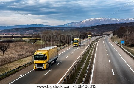 Fleet Of Yellow Trucks In Line As A Convoy At A Rural Countryside Highway Under A Beautiful Blue Sky