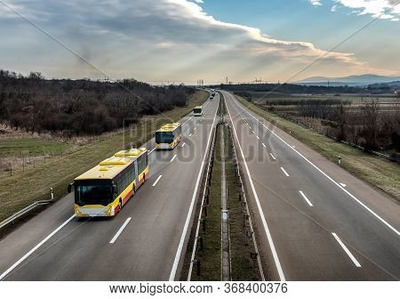 Intercity Yellow Line Buses In Line Traveling On A Rural Country Highway. Bus Passenger Transportati