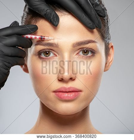 Young caucasian woman getting botox cosmetic injection in a forehead. Beautiful woman gets botox injection in her face. Adult girl gets cosmetic injection of botox in a clinic. Beauty treatments