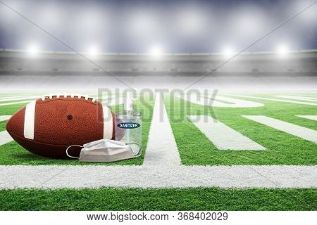 Football On Field Of An Empty Stadium With Hand Sanitizer And Medical Face Mask. Concept Of Football