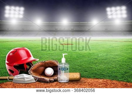 Baseball Equipment On Field Of An Empty Stadium With Hand Sanitizer And Medical Face Mask. Concept O