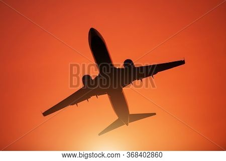 Air Travel Theme. Passenger Commercial Airplane During Take Off From Local Airport. Reddish Sunset S