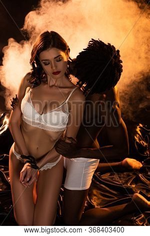 Handsome Seductive African American Man Hugging And Kissing Woman With Bound Hands On Bed In Dark Wi