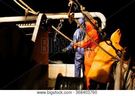 Fishermen choose a trawl with fish aboard at night in the Sea of Japan