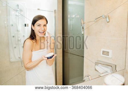 Young Woman Spreading Hydration Products,skincare Routine At Home.daytime Facial Creme.removing Make