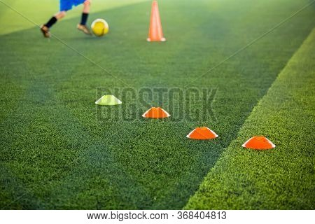 Selective Focus To Marker Cones Are Soccer Training Equipment On Green Artificial Turf With Blurry K