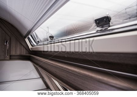 Modern Recreational Vehicle Camper Van Or Travel Trailer Rounded Window And Shades Close Up.