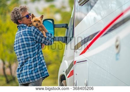 Retired Woman On The Road Trip With Her Small Breed Australian Silky Terrier Dog. Class C Motorhome.