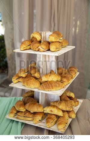 A Wooden Tray On A Wooden Table Full Of Sandwiches Under The Lights With A Blurred Background