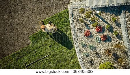 Landscaping And Gardening. Aerial View Of Gardener Installing Brand New Grass In Newly Developed Res