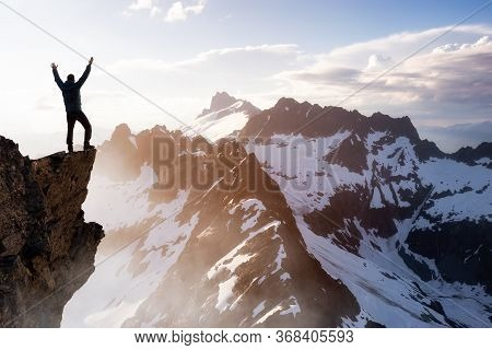 Fantasy Adventure Composite With A Man On Top Of A Mountain Cliff With Dramatic Landscape In Backgro