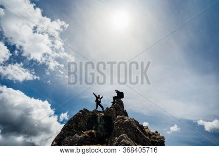 Young Backpacker Hiker Couple Climbing On The Peak Of Mountain Cliff.active Hiking Trip Lifestyle.va
