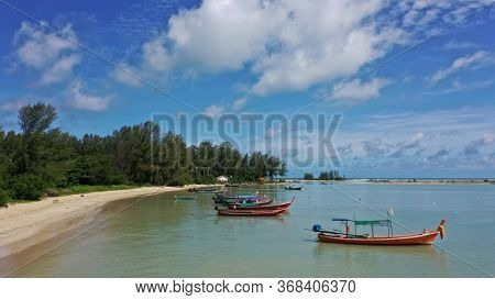Beautiful beach in Thailand with palm trees and traditional boats on a sunny day