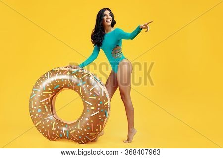 Full Lenght Image Of Sexy Fit Woman Dressed In Swimsuit Posing With Inflatable Point Finger Away On