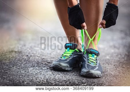Sporty female runs outdoor, photo of a sportswoman crouched to tie shoelaces, workout, happy healthy lifestyle, summer activity