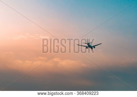 Aircraft flying over clouds, aviation sunset background, essential transport for business and travel