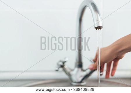 Woman Hand Opening Silver Faucet Or Water Tap With Metal Washing Sink In The Kitchen .