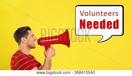 Young Man With Megaphone And Text Volunteers Needed On Yellow Background