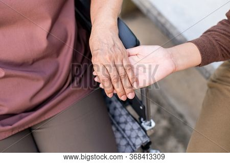 Caregiver Hands Holding To Asian Elderly Woman Sitting On Wheelchair,take Care And Support,senior In
