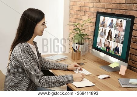 Woman Having Video Chat With Colleagues At Table In Office. Team Work