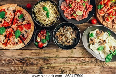 Table Of Italian Meals On Plates Pizza, Pasta, Ravioli, Carpaccio, Mushroom Risotto, Caprese Salad A