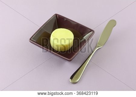 Pat Or Pad Of Butter In Purple Dish With Butter Knife On Lavender Background