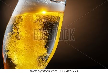 Jet of beer is poured into a beer glass, causing a lot of bubbles and foam. Dark brown background.