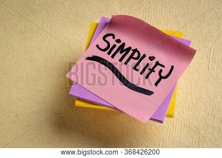 simplify reminder, pragmatic, declutter or get organized concept,  - black ink handwriting on a sticky note
