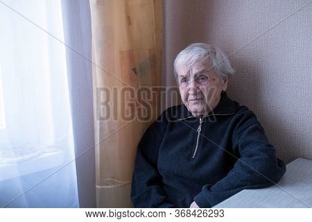 Portrait of an elderly depressed woman. Pensioner in her house.