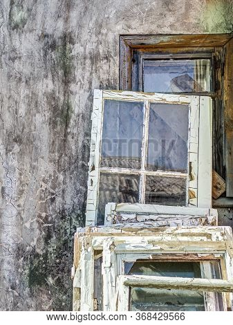 Old Window Frames With Cracked And Peeling Paint Near The Wall Of Abandoned Building