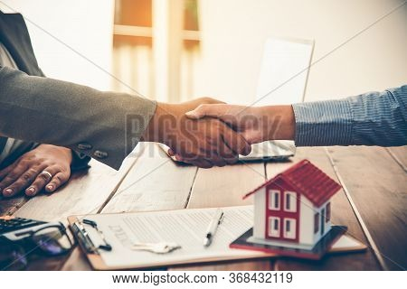 Real Estate Agents And Clients Join Hands To Congratulate Them On Achieving Contractual Agreements,