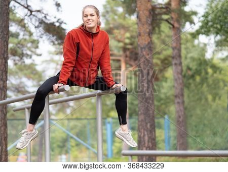 Attractive Blond Fit Caucasian Girl Sitting On Parallel Bars In Sports Area Outdoor In Summer. Woman