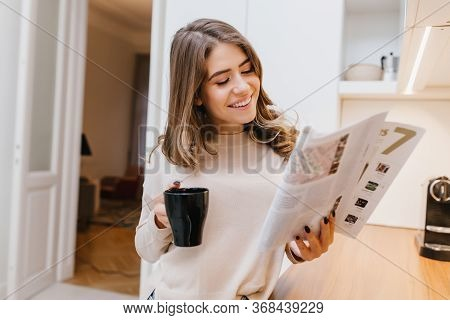 Magnificent Girl Reading Magazine With Smile In Her Room. Portrait Of Curious Brunette Lady With Bla