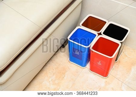 Garbage Classification Bins Near A Sofa In A Parlour At Home English Translation For The Lables-blue